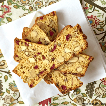 vegan biscotti thins stacked on top of parchment paper over a colorful napkin