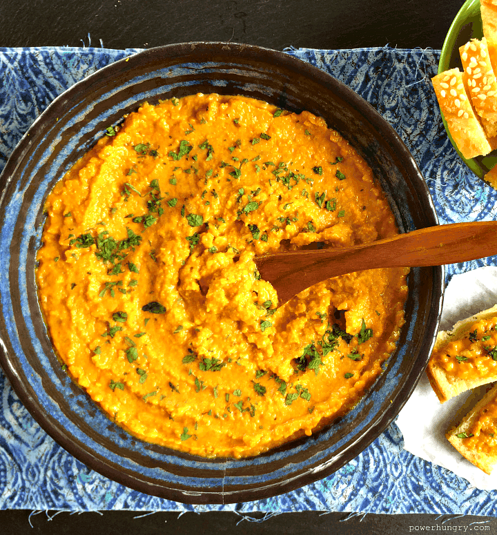 red lentil dal spread in a blue bowl with a wooden spoon