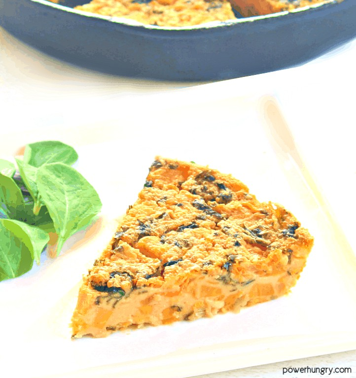 Sweet potato and kale chickpea flour frittata slice on a white plate