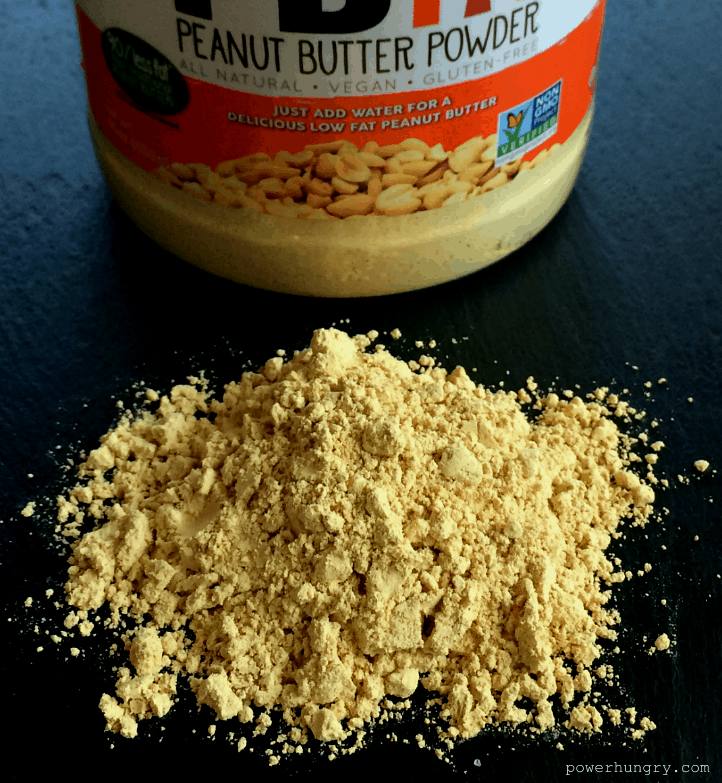 peanut butter powder on a piece of slate with the jar of peanut butter powder in the background