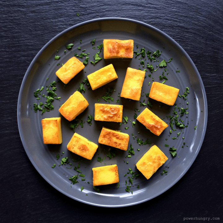 chickpea flour tofu cubes on a grey plate with chopped herbs
