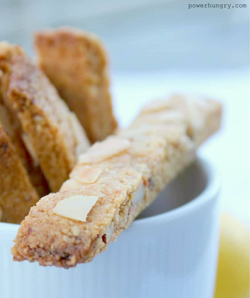 close-up of almond coconut flour biscotti in a white mug with a lemon in the background