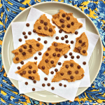 pieces of vegan chocolate chip cookie brittle on a grey plate