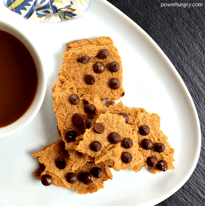 pieces of vegan chocolate chip cookie brittle on a white plate with a cup of coffee alongside