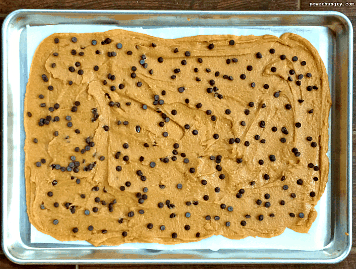 cookie brittle sough spread out on a baking sheet and sprinkled with chocolate chips