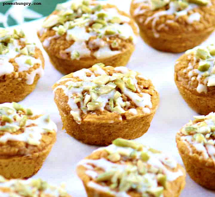 vegan pumpkin latte muffins topped with a drizzle of white chocolate and chopped pepitas