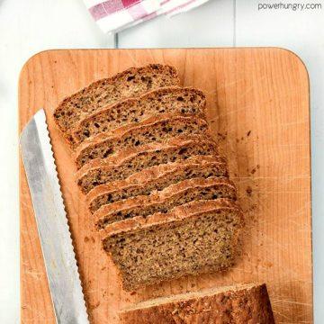 mini loaf of walnut oat blender bread, sliced, on a wooden cutting board