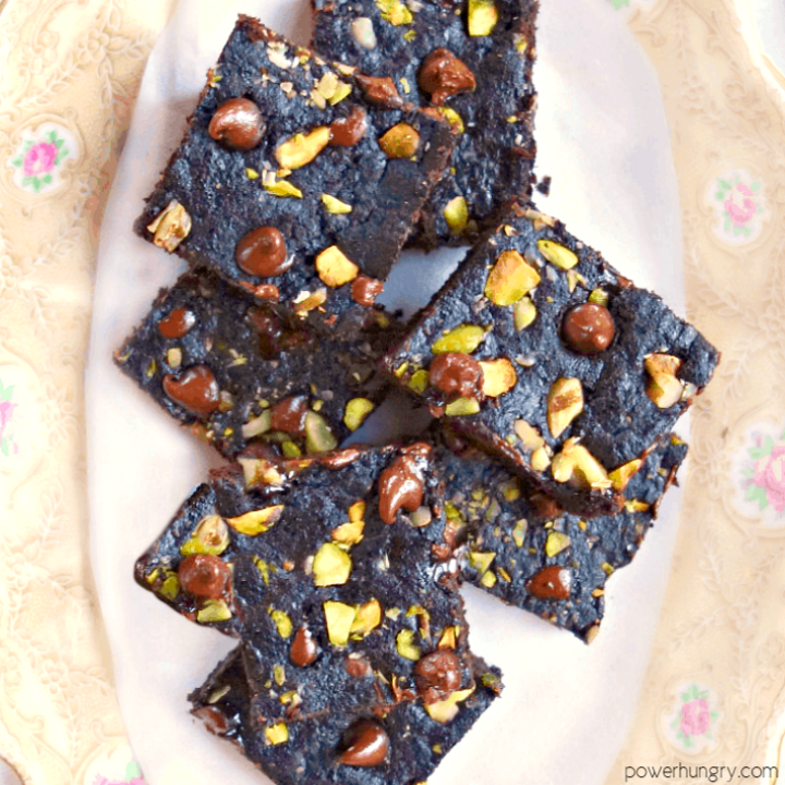 vegan tiger nut flour brownies, studded with chocolate chips and nuts, on a china plate