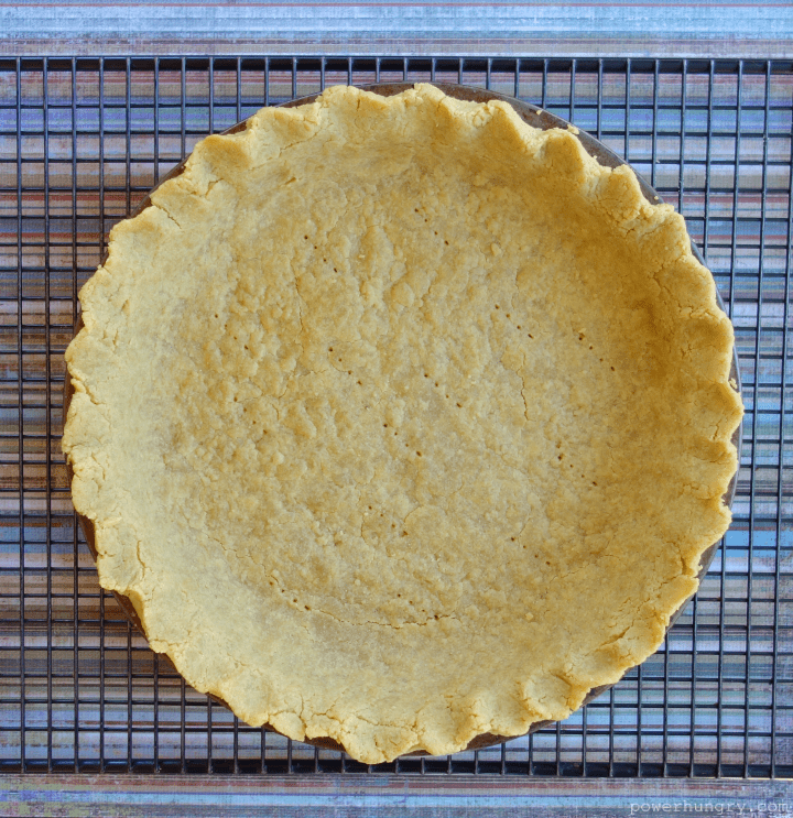 Overhead shot of baked chickpea flour pie crust on black cooling rack