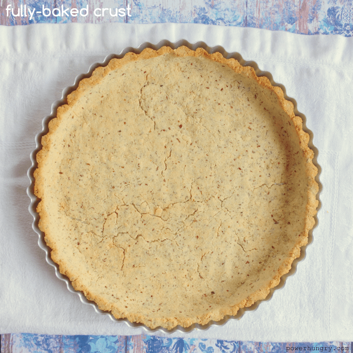 baked coconut-almond flour pie crust on a piece of white parchment paper