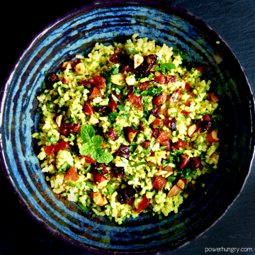 jeweled cauliflower rice in a blue pottery bowl with a black background