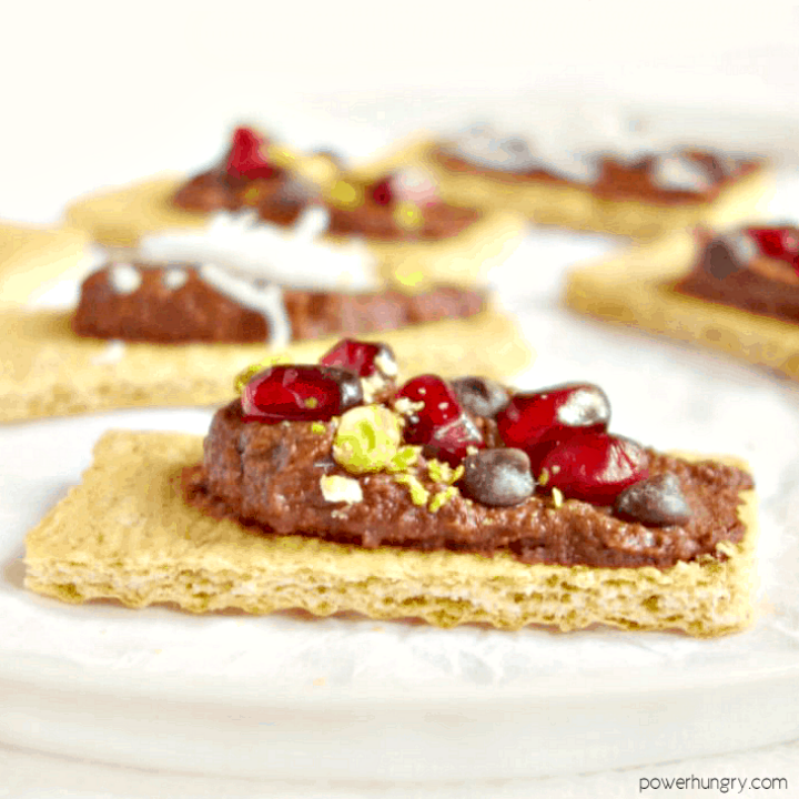 brownie batter hummus spread on graham crackers and topped with pomegranate seeds and chopped pistachios