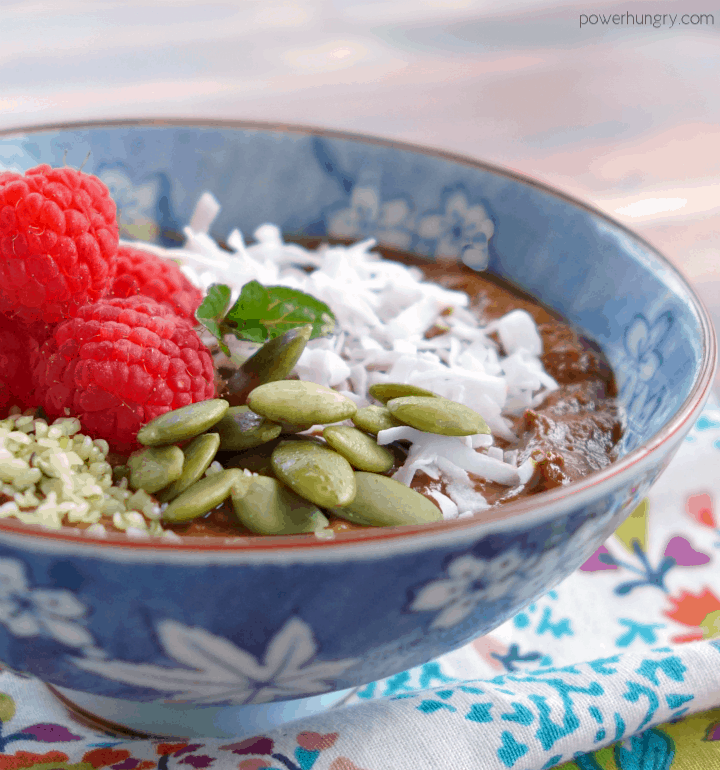 chocolate pumpkin pudding in a small blue and white bowl , with assorted toppings