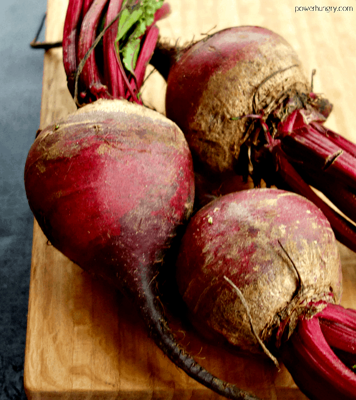 3 medium-large raw beets on a cutting board