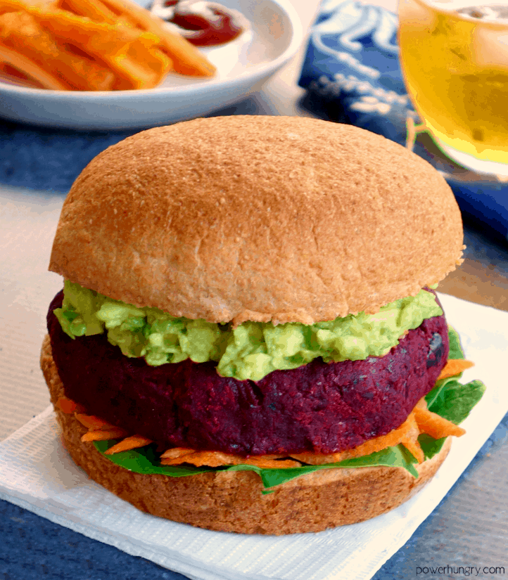Vegan beet burger on a bun with mashed avocado and vegetables