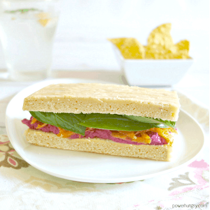 fluffy red lentil bread sliced and used in a sandwich with spinach and hummus