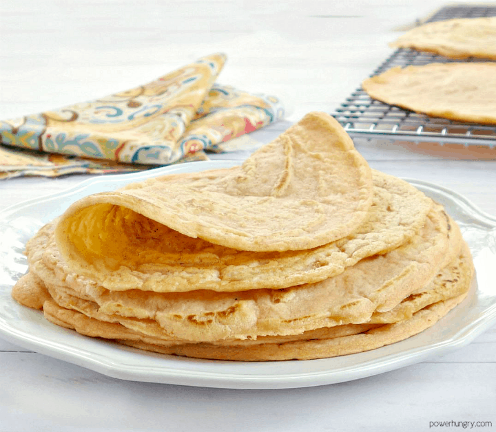 a stack of red lentil tortillas on a white plate