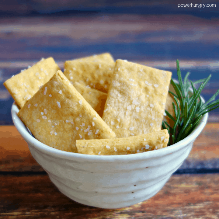 white bowl filled with vegan cheese chickpea flour crackers and a sprig of rosemary