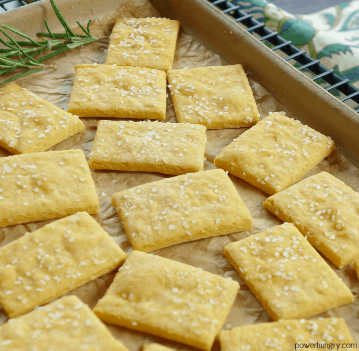 cheese-y chickpea flour crackers topped with sea salt on a pottery baking sheet lined with parchment paper.