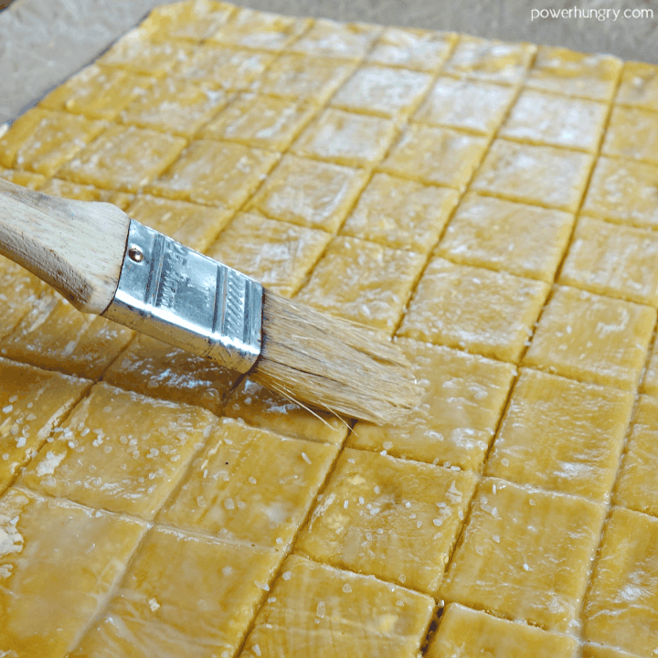 unbaked cheese-y chickpea flour crackers being brushed with water