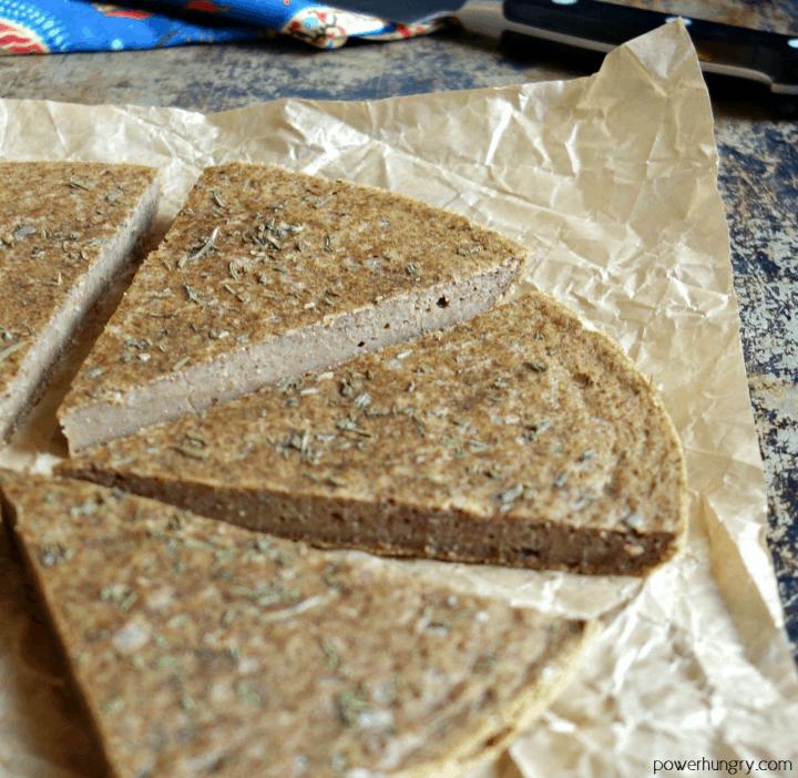 wedges of vegan lentil flatbread on a piece of brown parchment paper
