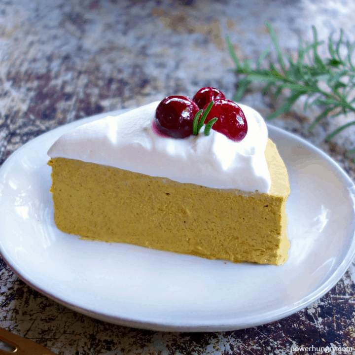a slice of vegan hemp heart pumpkin cheesecake, topped with coconut whipped cream and sugared cranberries, on a white plate