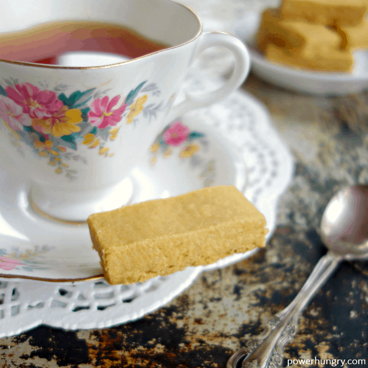 Chickpea shortbread cookie on the saucer of a floral teacup and saucer set.