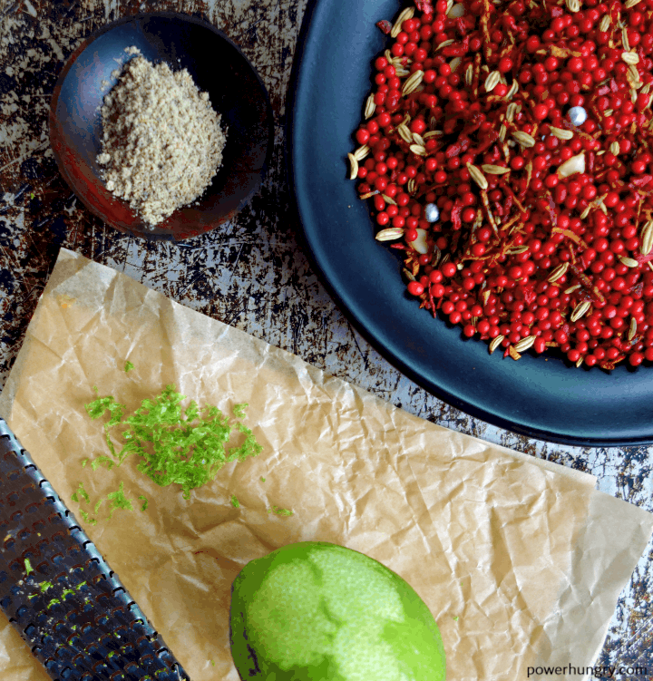close up of lime zest, muhkwas, lime zest and cardamom on a sheet pan