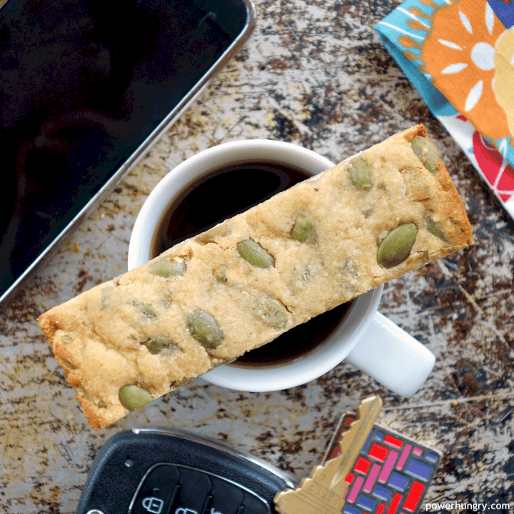 overhead shot of a grain-free granola bar perched on top of a cup of coffee, with keys, a phone and a floral napkin nearby