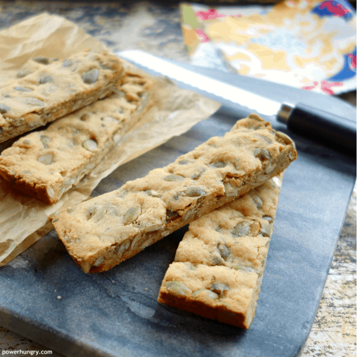 Vegan grain-free granola bars on a marble cutting board with a knife and napkin in the background