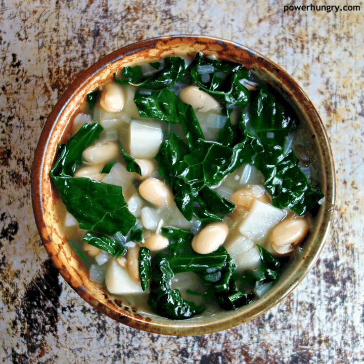 overhead shot of Kale Potato & White Bean Soup in a pottery bowl