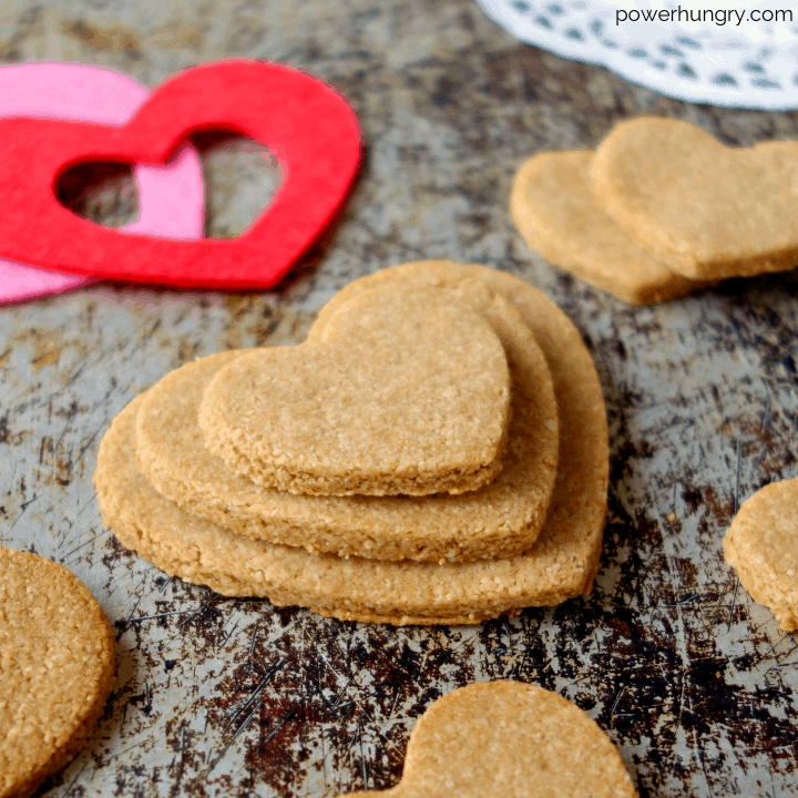 2-ingredient almond flour cut out cookies in the shape of hearts on an aged metal background