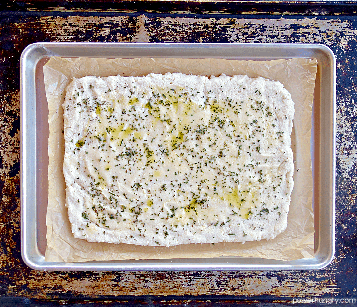 unbaked white bean flatbread on a parchment paper-lined baking sheet