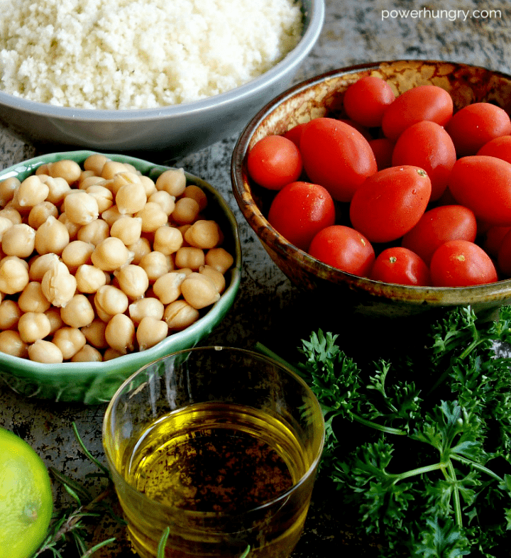 ingredients for chickpea tomato and cauliflower salad laid out on a baking sheet