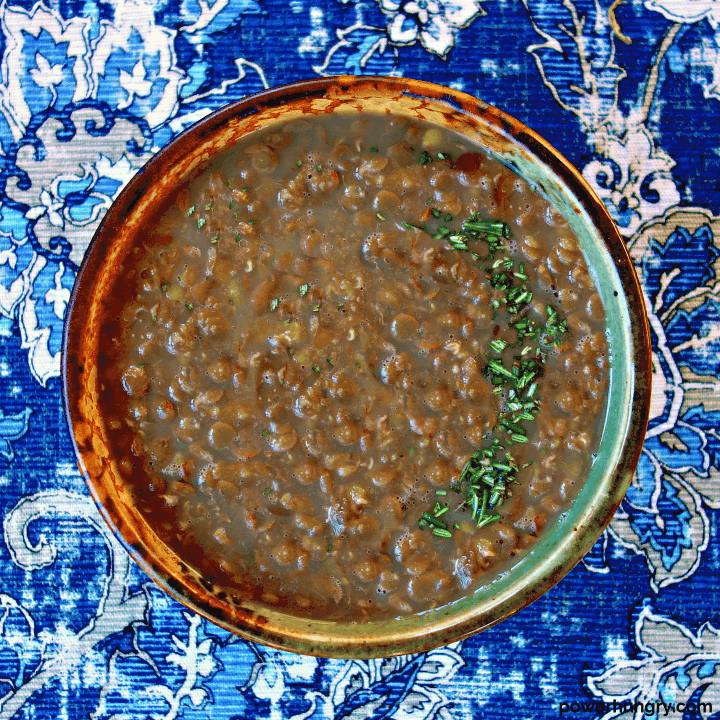 overhead shot of 3-ingredient lentil soup in a pottery bowl atop a blue napkin