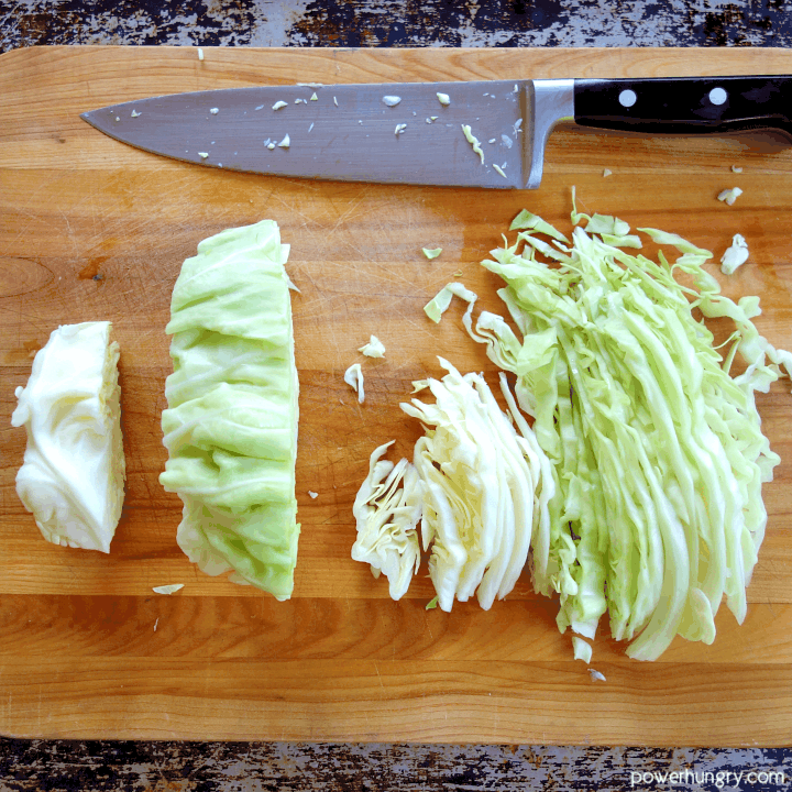 green cabbage on a wooden cutting board being cut into thin strips to make cabbage noodles