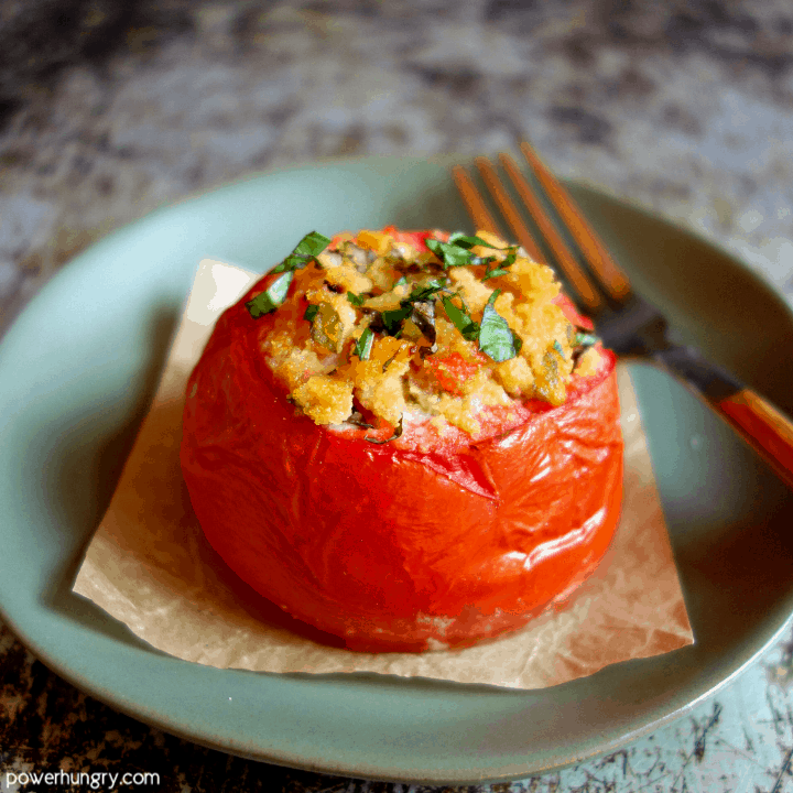 Stuffed tomato, made with coconut flour, on a piece of parchment paper on an olive colored plate