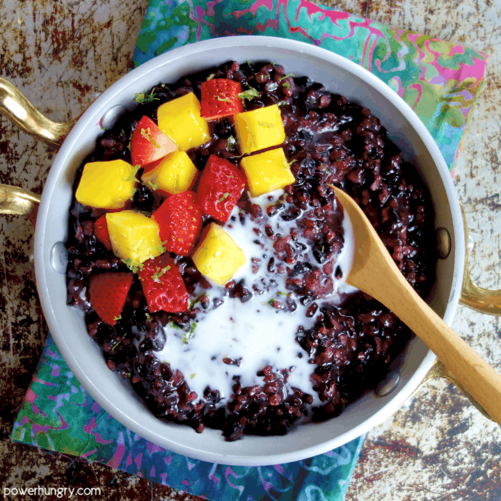 overhead shot of coconut black rice pudding in a silver and gold dish, all atop a colorful napkin