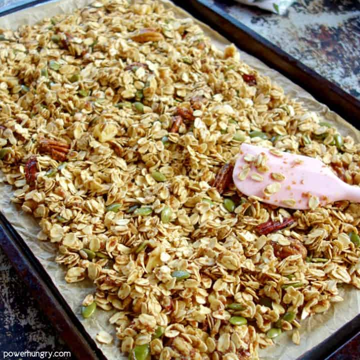 unbaked granola being spread on a baking dish with a pink spatula