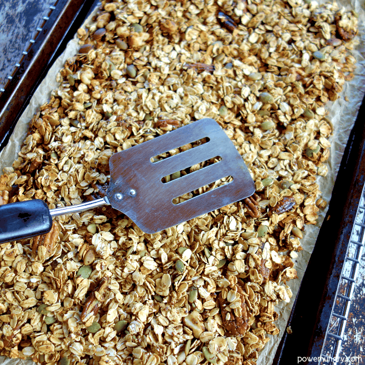 tamping down granola with a metal spatula after baking