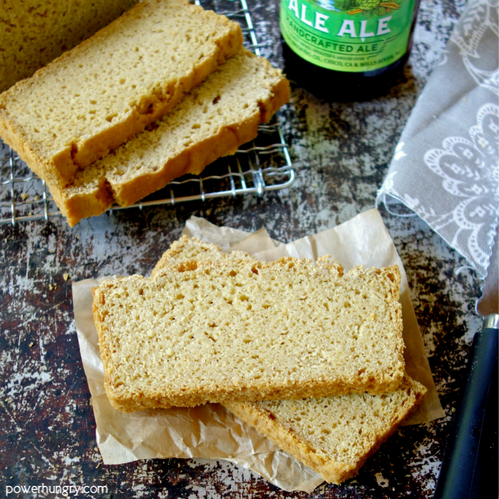 Slices of chickpea flour beer bread with a knfie and bottle of beer