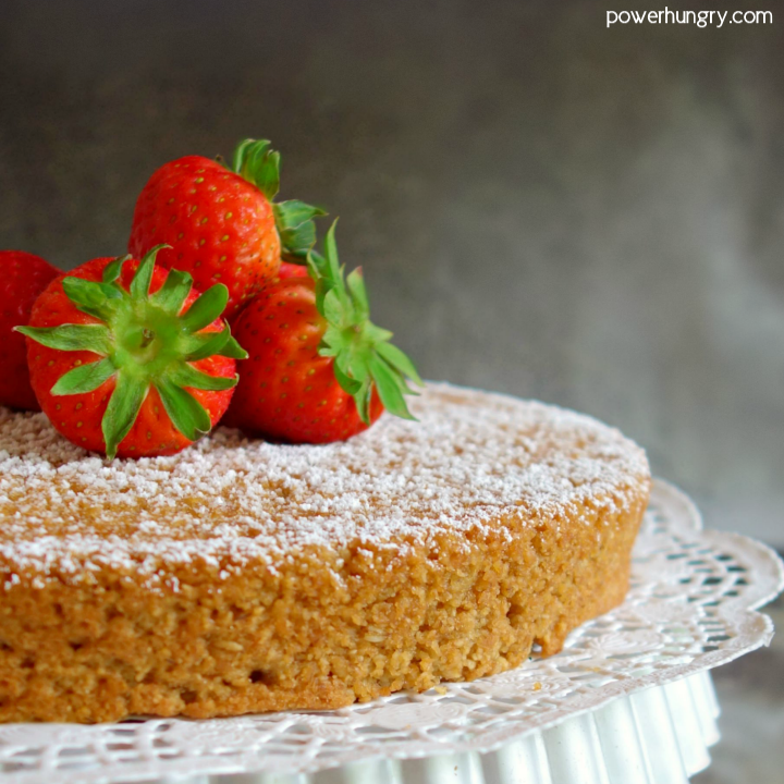 Vegan almond flour cake with strawberries on cake stand