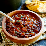 3-ingredient black bean vegan chili in a wooden bowl with cips in the background