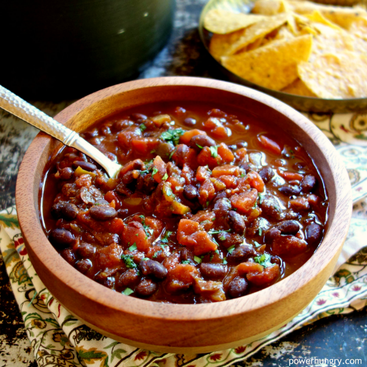 3-ingredient black bean vegan chili in a wooden bowl with chips in the background