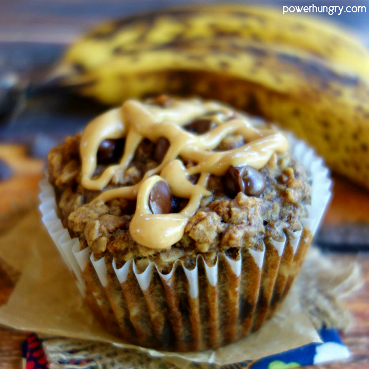 Peanut Butter Banana Baked Oatmeal Cup on a piece of parchment paper with bananas in the background