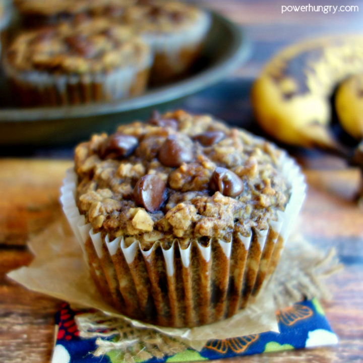 Peanut Butter Banana Baked Oatmeal Cup n floral napkin, with additional muffin cups and bananas in the background