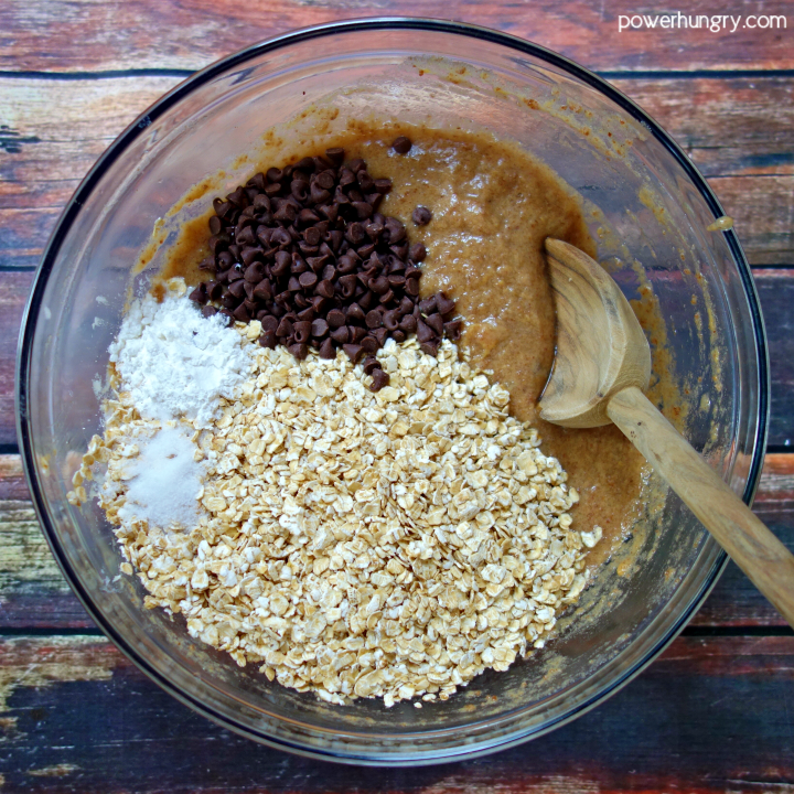 Dry ingredients added to glass bowl of wet ingredients for peanut butter banana baked oatmeal cups