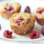 3 vegan raspberry almond flour muffins on a white plate with raspberries