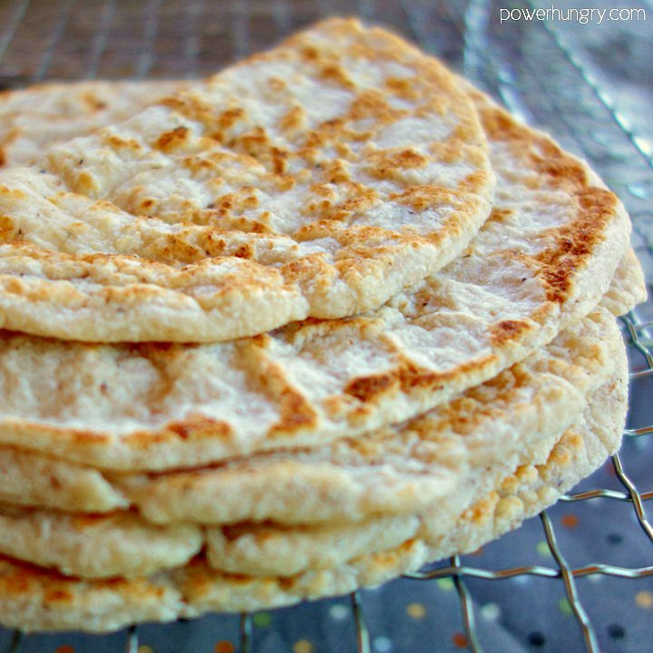 stack of coconut flour tortillas ona metal cooling rack, with the top tortilla folded
