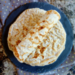 Rolled coconut flour tortilla on a stack of more tortillas
